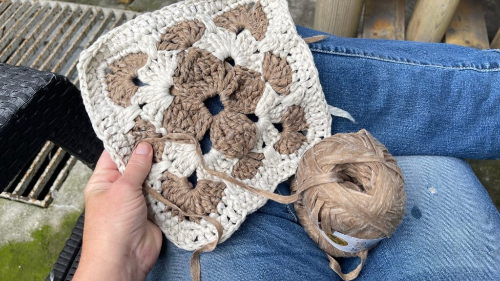 granny square in brown and white on leg
