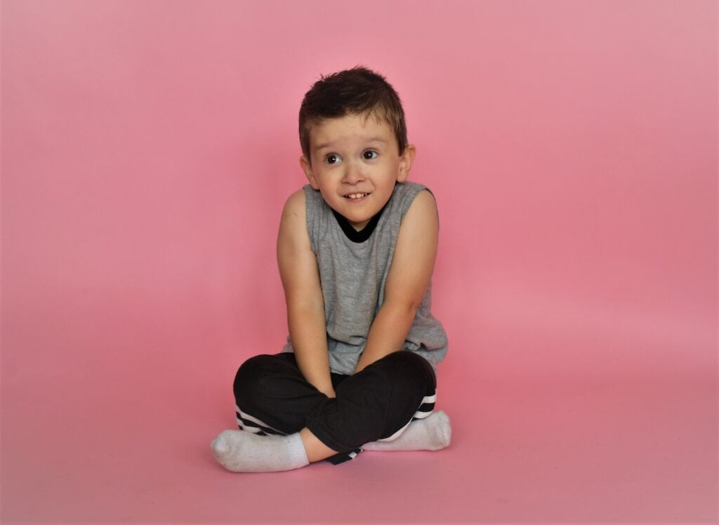 boy on pink background smiling wearing a grey shirt